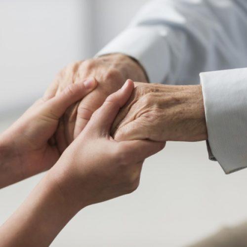 nurse-holding-senior-man-s-hands-sympathy_23-2148740011
